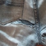 Hole in jeans edged with zigzag stitch.